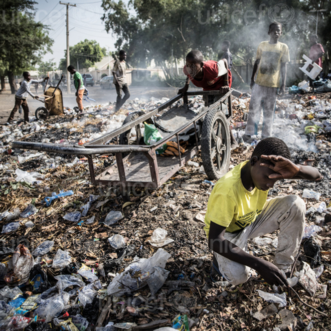 Muhammad Modu (yellow t-shirt, beige pants), 15, an internally displaced person from Malori, digs through a rubbish dump in Maiduguri, Nigeria for saleable items on March 24, 2016. Two years ago, Boko Haram attacked his village, and Muhammad and his family fled by foot with only the clothes on their backs. Today, Muhammed lives with his grandfather in Maiduguri and has been out of school for nearly two years. The rest of his family live in a nearby informal IDP camp. Scavenging garbage earns Mohammad approximately 40 Naira a day. Muhammad wants to be a solider when he grows up so he can fight Boko Haram. (Photo by Ashley Gilbertson / VII Photo for UNICEF)