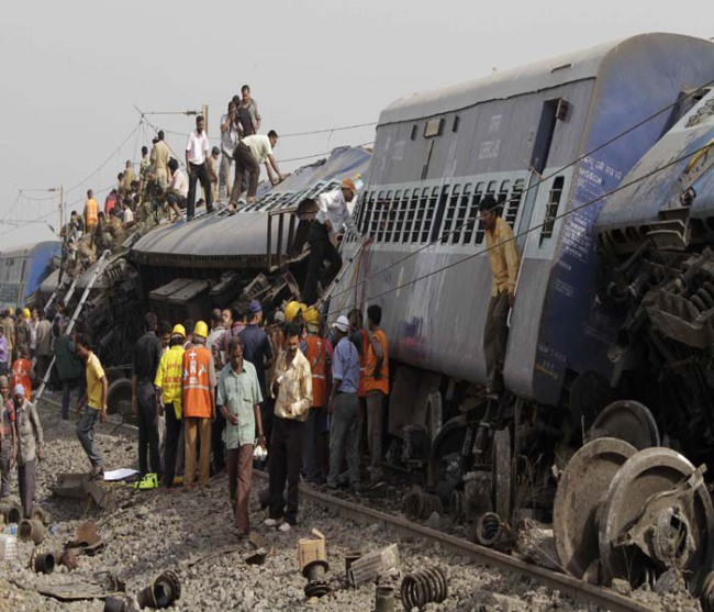India rescue workers gather at the scene of a train crash in Sardiha, West Bengal state, about 90 miles (150 kilometers) west of Calcutta, India, early Friday, May 28, 2010. The overnight passenger train was derailed by an explosion then hit by another train early Friday as it traveled through a rebel stronghold of eastern India, officials said. (AP Photo/Bikas Das)